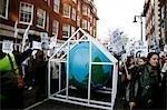 Lutte contre les changements climatiques. Manifestants marchant contre l'utilisation de combustibles fossiles et autres activités antiécologiques. Le globe dans la serre au centre représente l'effet de serre, la principale cause du réchauffement planétaire et le changement climatique.