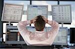 Je regarde écrans d'ordinateur homme d'affaires, avec les mains sur la tête, vue arrière.