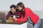 L'homme et la femme enceinte à l'aide d'ordinateur portable de magasiner en ligne à la maison