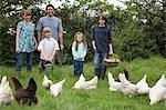 Parents with three children (5-9) feeding hens in garden, portrait