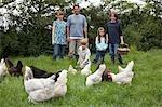 Parents with three children (5-9) feeding hens in garden