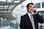 China, Hong Kong, business man using mobile phone, standing on footbridge