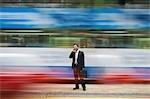 China, Hong Kong, business man using mobile phone, standing on street, long exposure
