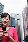 China, Hong Kong, woman text messaging on street