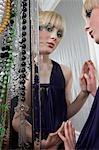 Teenage girl (16-17) in elegant dress reflected in mirror