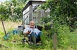 Senior man pouring drink, sitting in garden