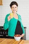 Pregnant woman drinking fruit juice in kitchen, portrait