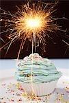 Single cupcake with lit sparkler