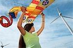 Girl (7-9) holding airplane kite at wind farm