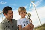 Junge (7-9) Blasen Spielzeug Windmühle mit Vater am Windpark
