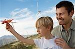Junge (7-9) halten Spielzeug Segelflugzeug mit Vater am Windpark
