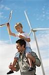 Junge Schultern (7-9) Betrieb Kite, sitzend auf Väter am Windpark