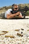 Mitrailleuse visée au polygone de tir de l'homme, se concentrent sur les balles en avant-plan