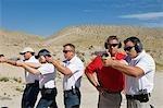Instructeur en aidant les hommes visant au polygone de tir de poing