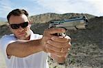 L'homme arme de poing visée au tir dans le désert
