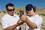 Instructeur assistant femme visant pistolet à tir dans le désert