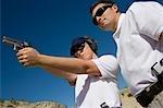Instructeur aider femme visant pistolet à tir, vue d'angle faible