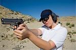 Femme visant pistolet à tir dans le désert