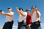 Instructeur en aidant les personnes visant des canons à tir