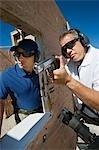Instructeur en aidant l'homme arme de poing visée au polygone de tir