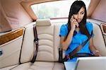 Jeune femme parlait au téléphone et en utilisant un ordinateur portable dans la voiture