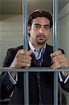 Homme debout derrière les barreaux de la cellule
