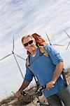 Senior man with bicycle near wind farm