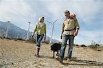 Senior couple walking with dog near wind farm