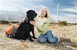 Senior woman with dog near wind farm
