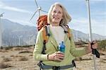 Senior woman with backpack near wind farm