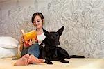 Teenage Girl-Lesebuch auf Bett mit Hund