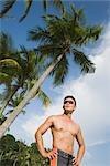 Mann mit Händen an den Hüften am Strand