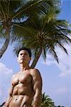 Musculaire homme extérieur en face de palmiers