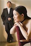 Femme rêverie avec homme debout en arrière-plan