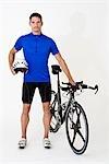 Un homme debout avec un vélo de course