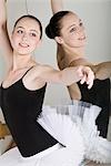 A ballet dancer posing next to a mirror in a ballet studio