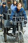 China,Beijing. Men transporting charcoal bricks in a local neighbourhood Hutong.