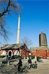 China, Peking, Tianningsi Tempel. Radfahrer vorbei an einen Tempel und ein Schornstein.