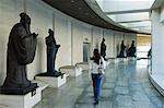 Chine, Beijing, China Millenium Monument Musée. Une fille est passant devant les personnages d'importance historique, y compris de Confucius. .