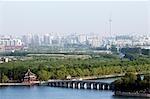 China, Peking. Sommerpalast - Unesco Weltkulturerbe. Die 17 Bogenbrücke und die Skyline der Stadt.