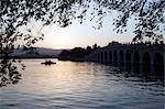 Chine, Beijing. Coucher de soleil l'été en palais patrimoine mondial UNESCO sur le lac Kunming et le pont 17.