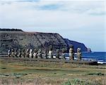 Quinze statues de Pierre colossales ou moais debout sur leur plate-forme, Ahu Tongariki, sur la côte orientale de l'île avec le dos à l'océan et les falaises de la péninsule de Poike derrière. À plus de 200 m de longueur, Tongariki est la plus grande plate-forme sur l'île de Pâques. Les statues sont jusqu'à 10 mètres de haut.
