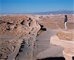 A tourist looks out over the Salt Mountain Range and the Atacama Desert from Las Cornicas ridge.