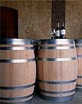 Bottles of Muga Reserva and Torre Muga on top of new wine barrels at Muga winery