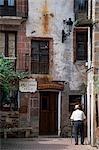 An old man walks down a quiet side street in Ezcaray