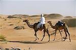 Un Bedu chevauche son chameau dans les dunes de sable dans le desertOman OM4John Warburton-Lee