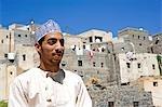 Oman, montagnes de Hajar de Western, Wadi Bani. Un village montagne éloignées de Balad Seet, un homme regarde vers l'extérieur avec sa maison traditionnelle derrière lui.