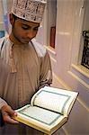 Oman, Muscat, Ghala, mosquée de Al Ghubrah (grande mosquée). Coran lecture au sein de la mosquée par un jeune homme omanais portant un chapeau traditionnel embroirdered (kumah) et un dishdasha avec un gland (furakha), parfois parfumée de la lotion après rasage.