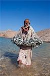 Oman, Mascate région, Bandar Khayran. Un vieux pêcheur des poissons pour les sardines avec un filet traditionnel d'une plage sur la côte près de Muscat