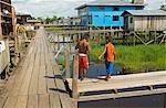 Peru,Amazon River. Boys fishing off the stilted walkway in the village of Islandia.